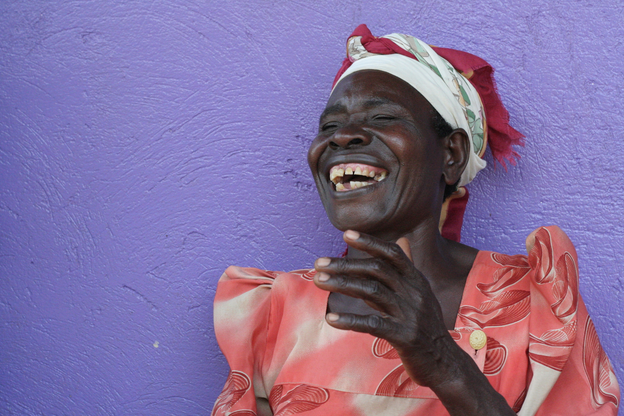 Woman laughing in front of a purple wall