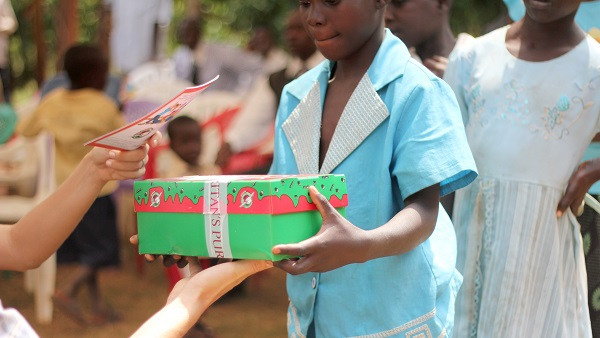 A woman giving a gift to a young girl