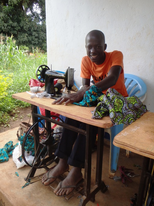 Young man at a sewing machine smiling
