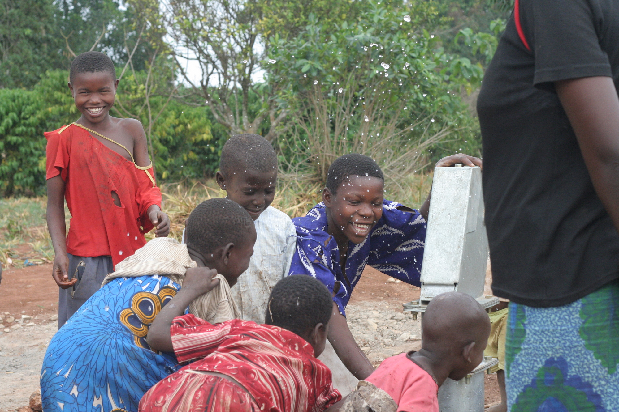 A group of kids at a water pump smiling