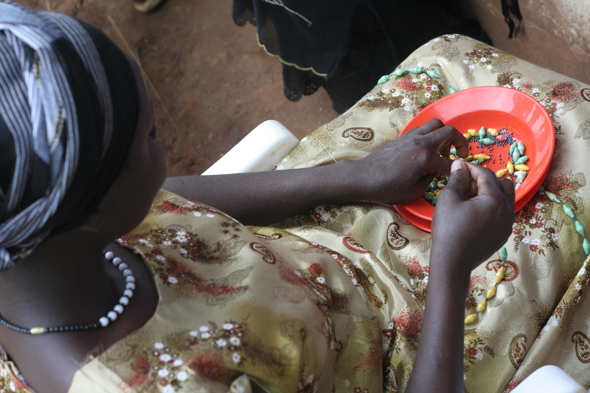 Woman stringing beads in her lap