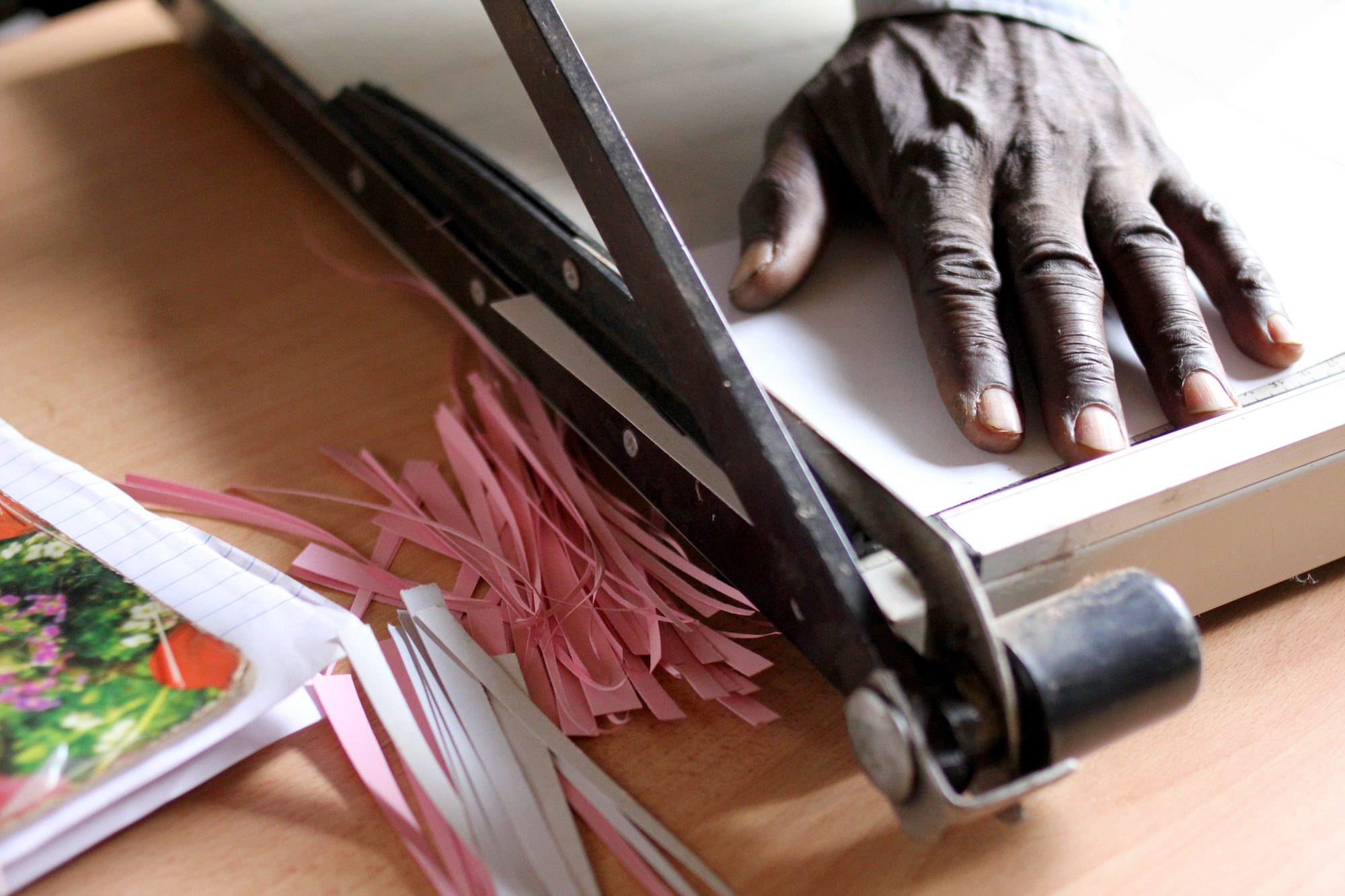 Man cutting strips of colored paper with a paper cutter