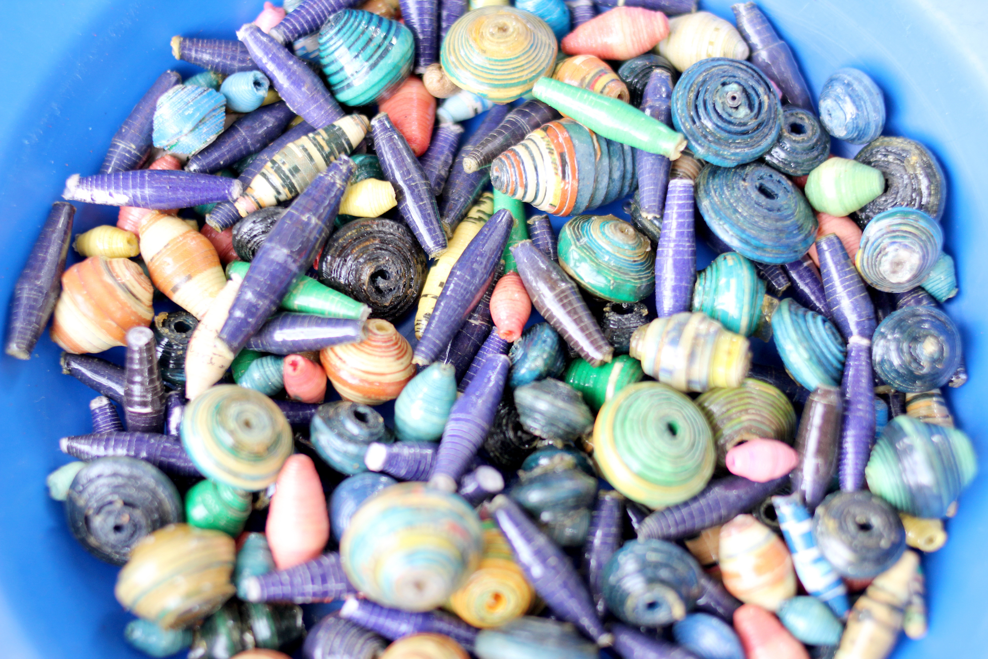 Closeup of colorful beads in a blue bowl