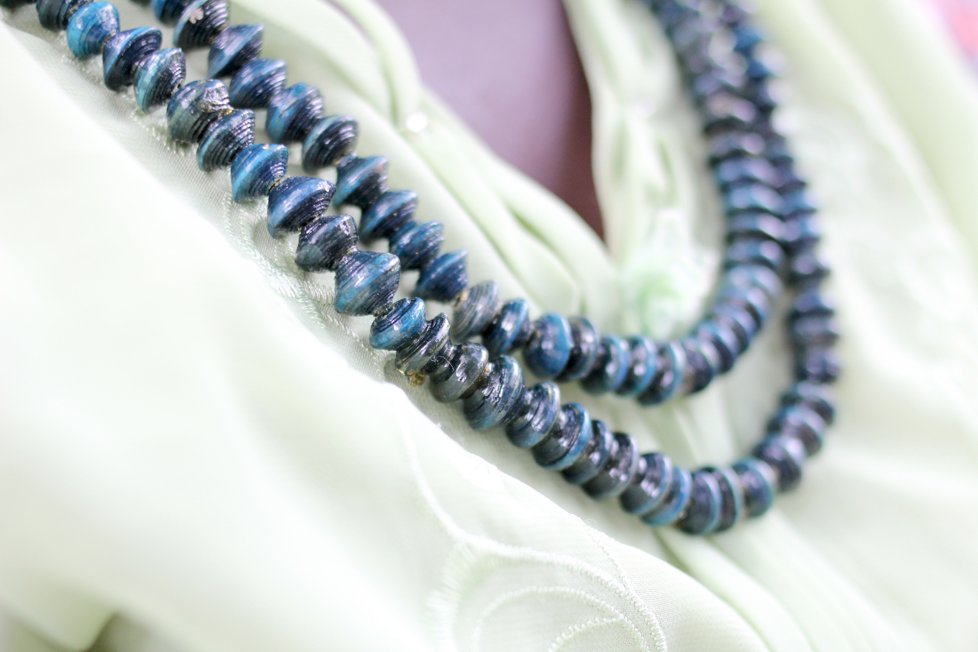 Close up of bead strands around a woman's neck