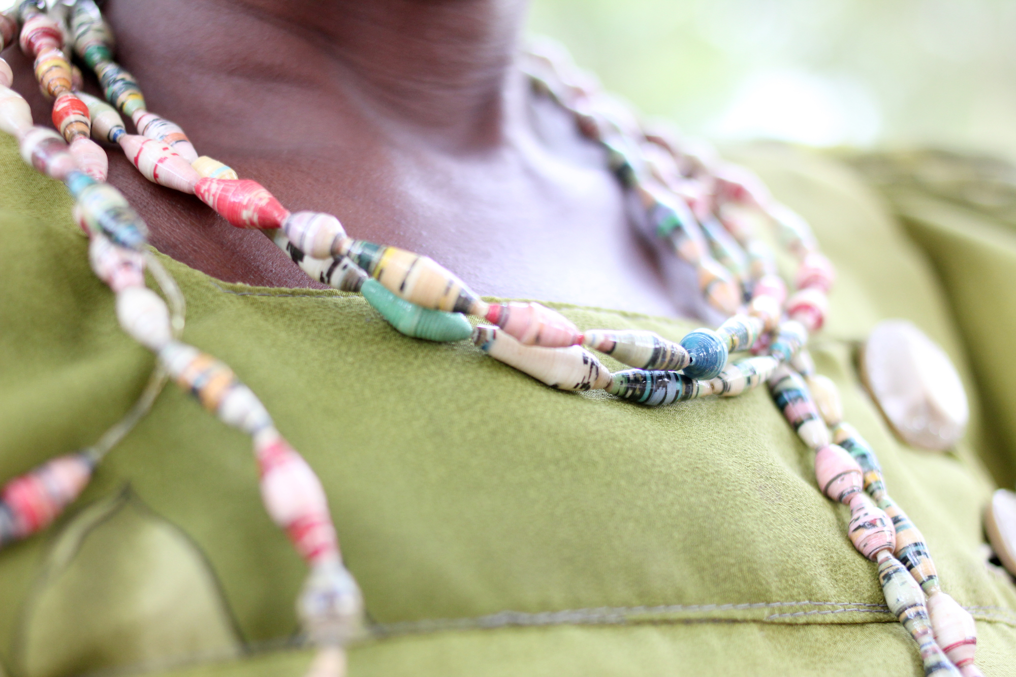 Close up of strands of beads around a woman's neck