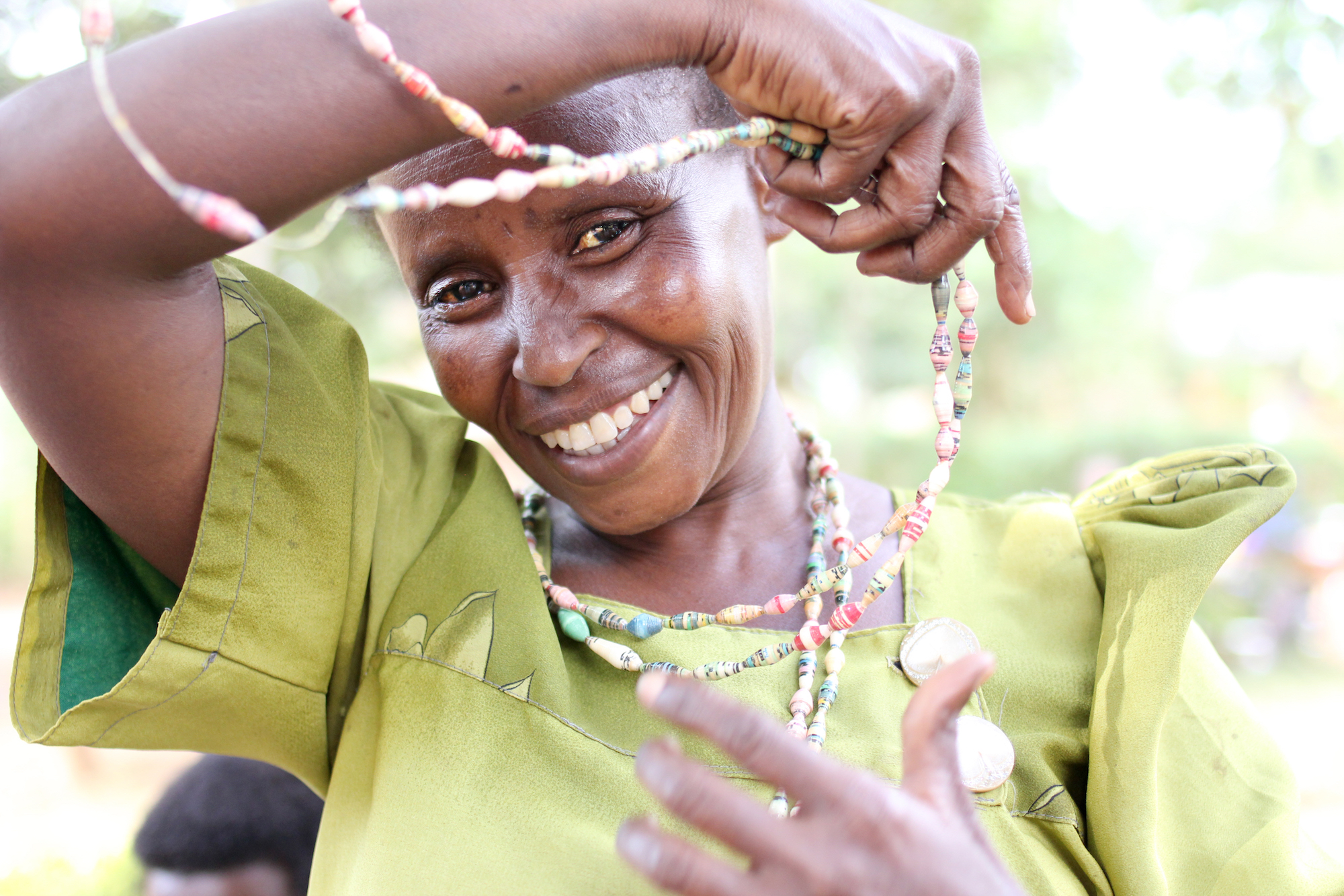 Smiling woman putting strands of beads over her head