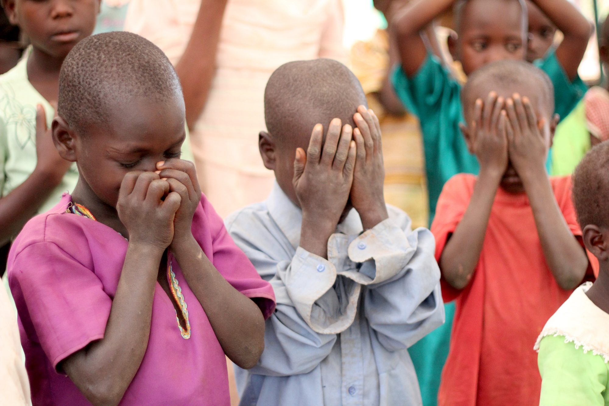 Group of children covering their eyes