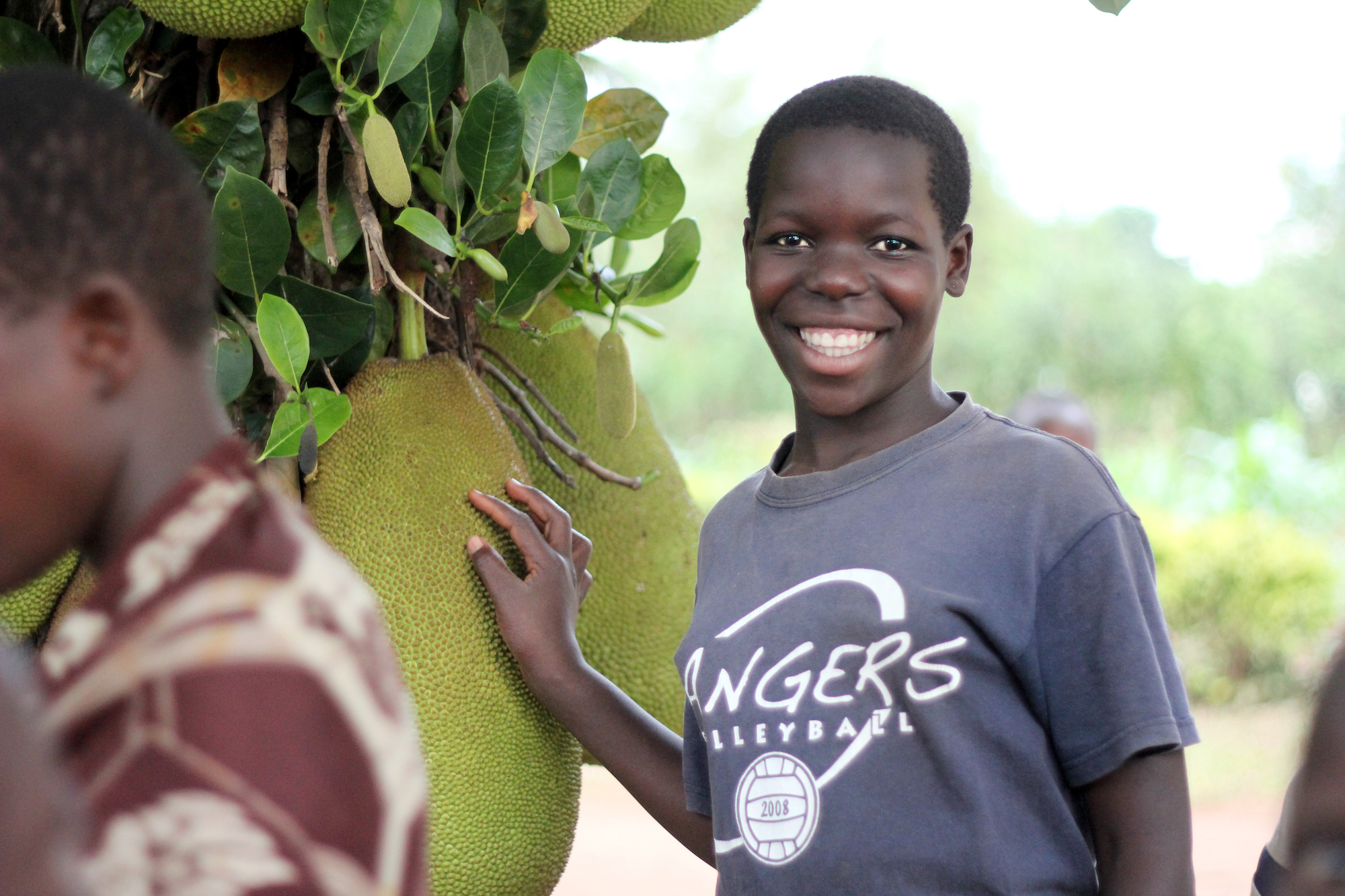 Young woman standing under a breadfruit tree