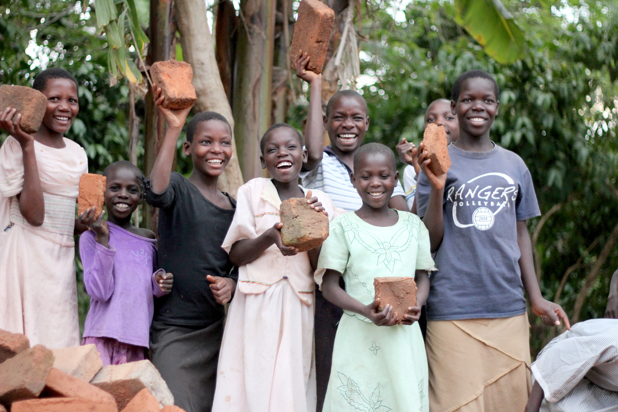 Group shot of smiling young people holding up bricks
