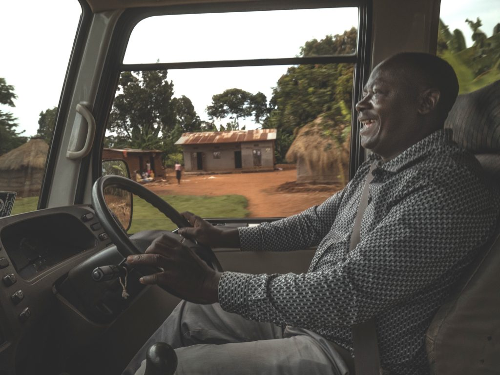 A man happily driving a bus in Uganda
