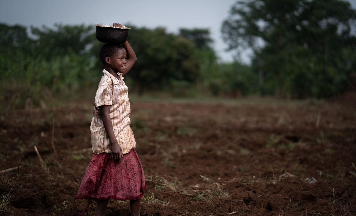 Child in Uganda carrying a basket of maize on their head