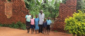 A grandfather with 4 of his grandchildren standing next to a broken wall in Uganda