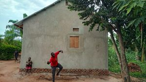 A young man playing dancing next to his new home in Uganda