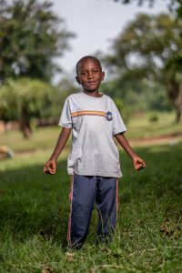 A young boy standing on grass in Uganda