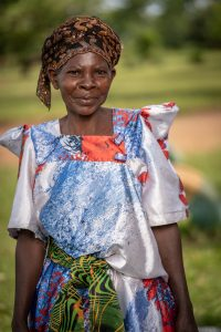 A closeup of a smiling woman in a colorful dress in Uganda