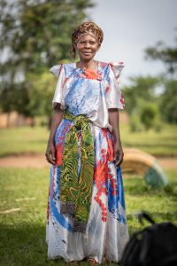 A smiling woman in a colorful dress standing in a field in Uganda