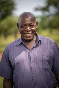 A smiling man in a blue shirt standing under a tree in Uganda