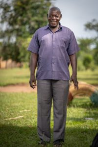 A man in a blue shirt standing in the shade in Uganda