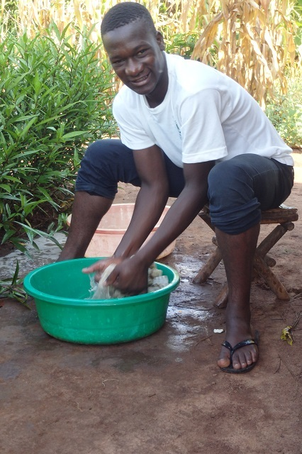 Young man washing his hands smiling at the camera